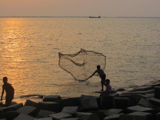 夕日に染まるメグナ川に網を投げる漁師