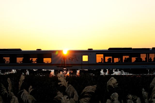 日本海に沈む夕陽を眺めるリゾートしらかみ