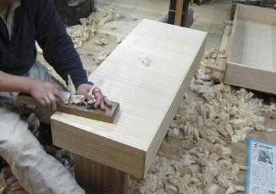 桐たんすの折っさし下引き出しの底を鉋で削る