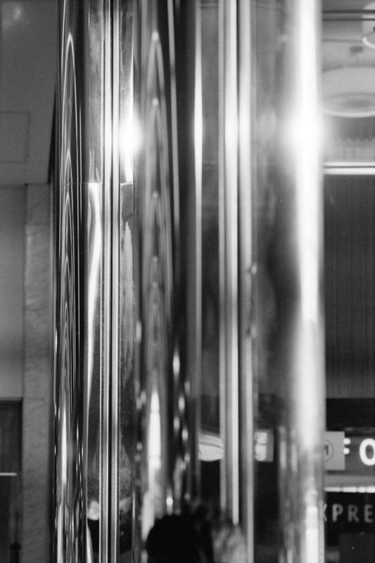 金属の円柱が周りの空間を映しこんでいる